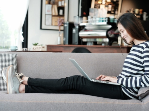 beautiful-asian-girl-using-laptop-computer-while-sitting-on-sofa-with-smiling-face-emotion_7190-694